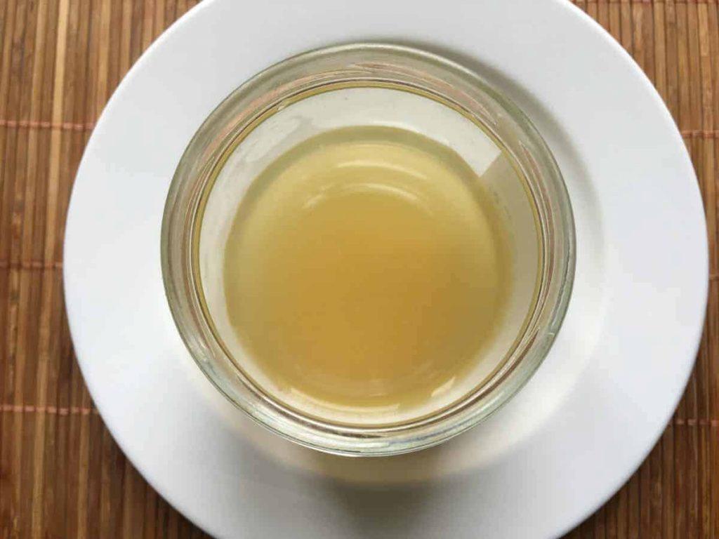 De l'aquafaba dans un bocal sur une assiette blanche