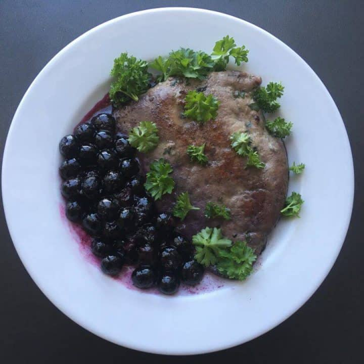 Liver and blueberries on a white plate