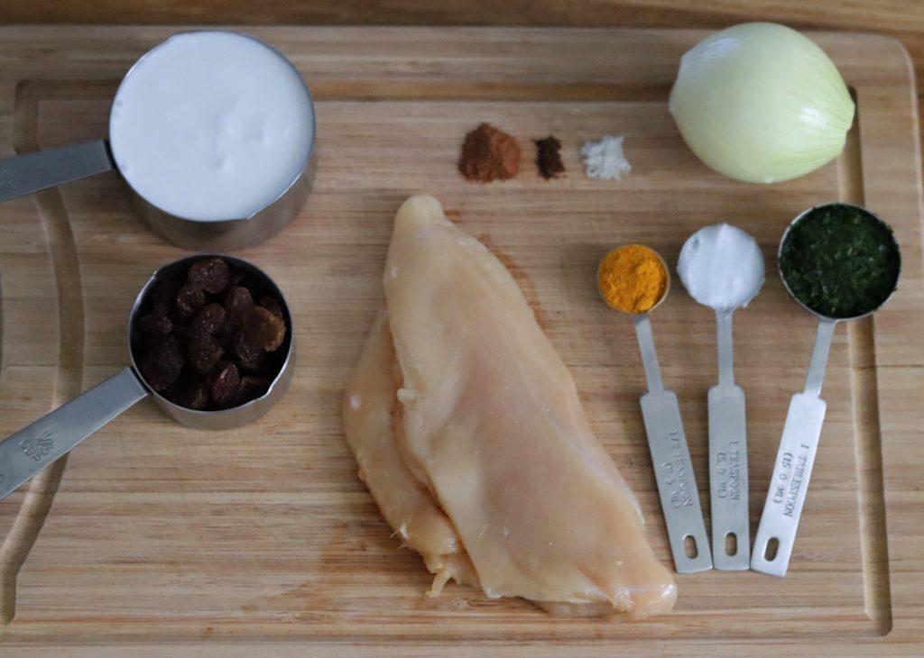 tous les ingrédients de la recette de poulet au curry exposés sur une planche en bois
