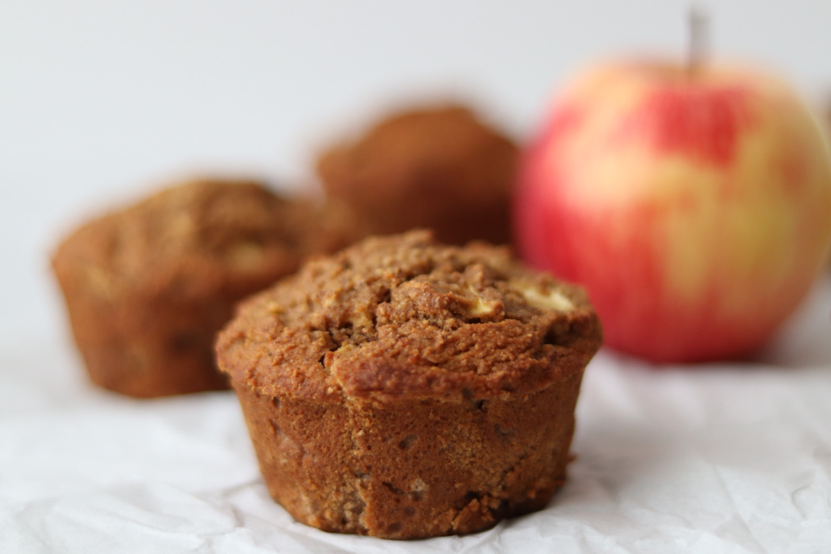 3 apple cinnamon muffins and an apple on a white sheet