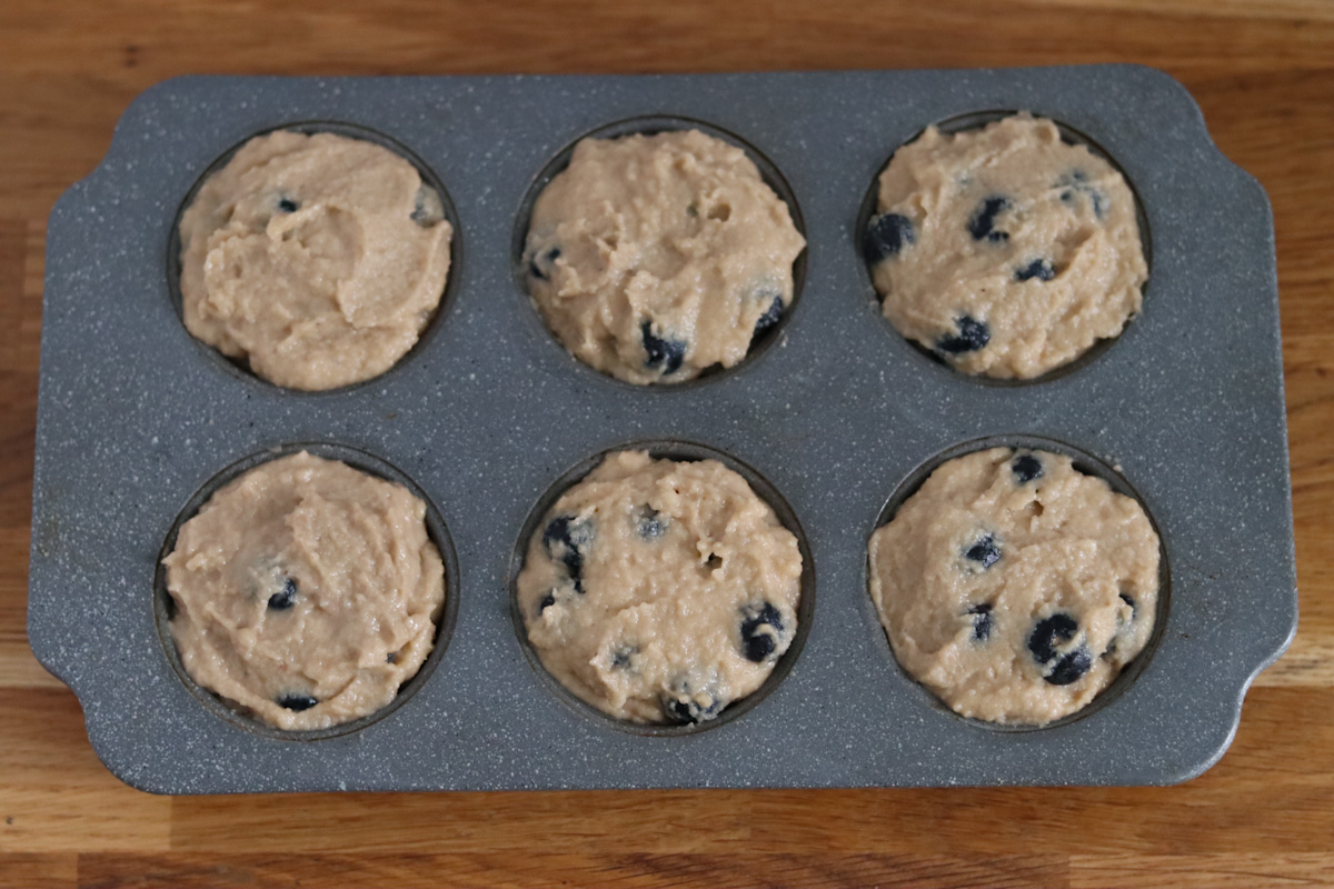 banana blueberry muffins batter in a muffin pan