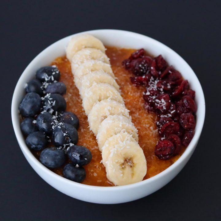 sliced banana, blueberries and dried cranberries on top of butternut squash puree in a white breakfast bowl