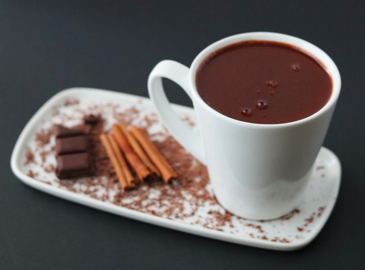 a white mug full of hot chocolate on a white plate with 4 cinnamon sticks and a chocolate bar and chocolate sprinkles to decorate the plate