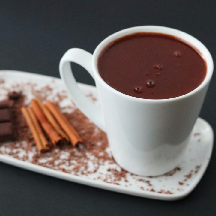 a cup of hot chocolate on a white plate with cinnamon sticks and a chocolate bar