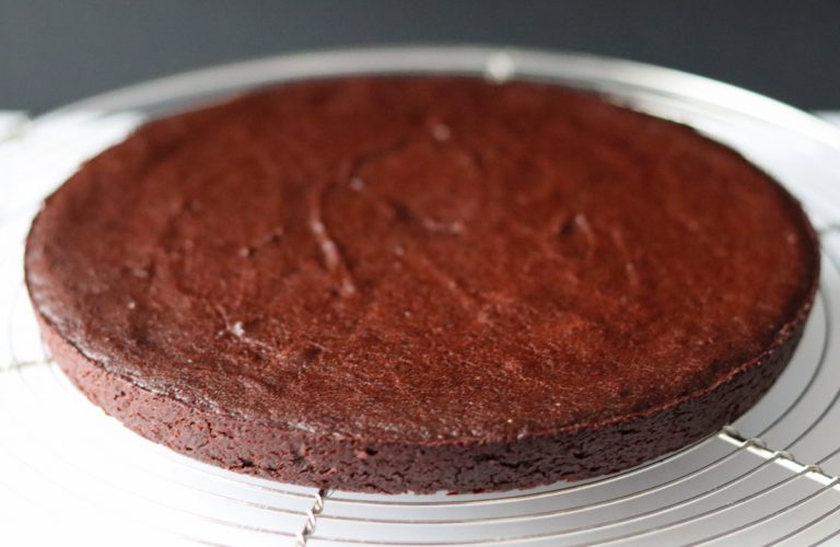 a fudgy chocolate cake on a baking rack