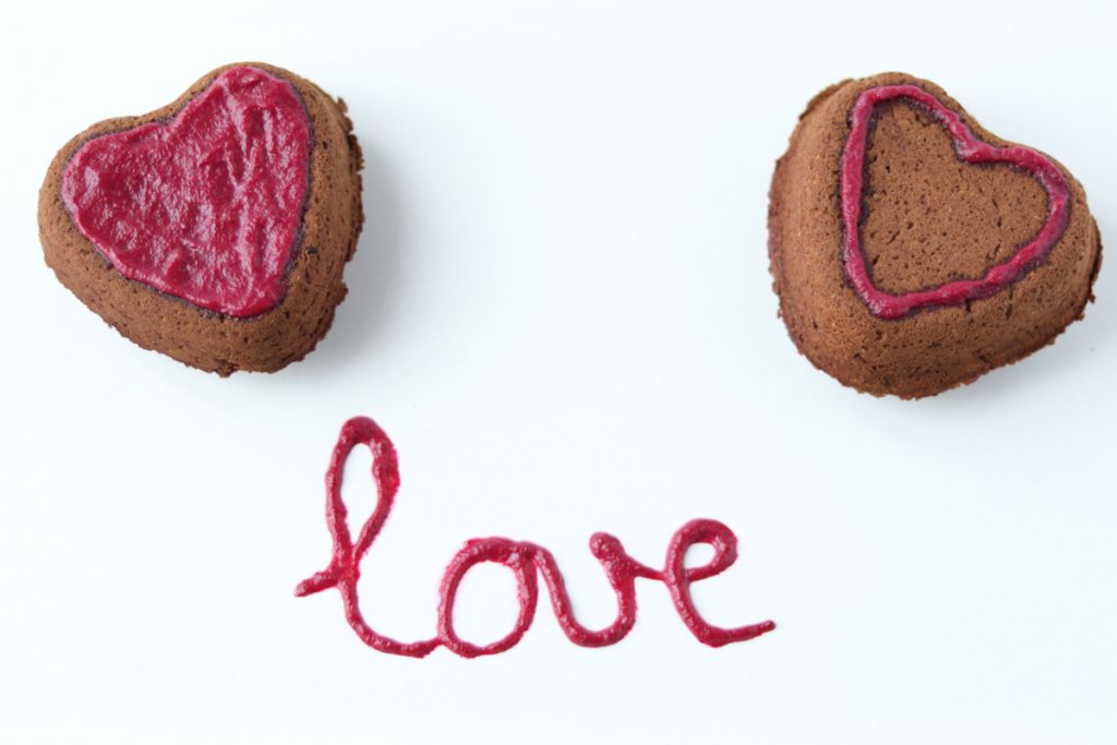 2 heart shaped chocolate cakes with no dye pink frosting on top and the word love written with the frosting on the plate.