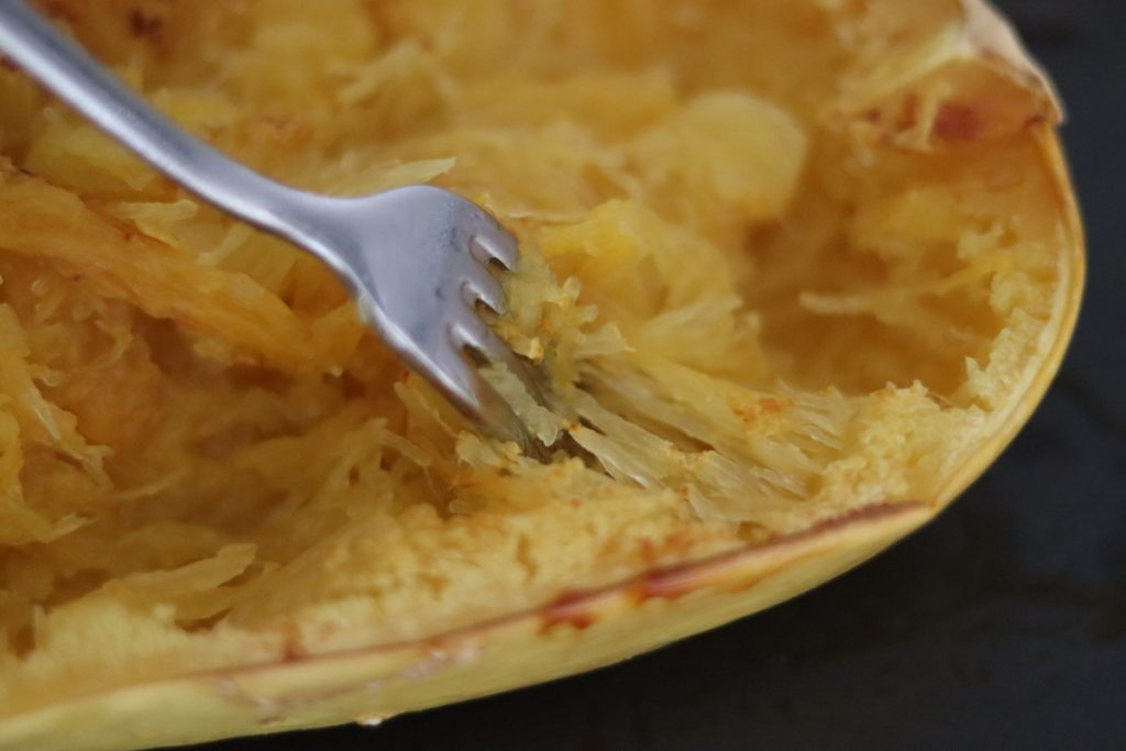 une fourchette en train de gratte la chaire d'une courge spaghetti pour obtenir la texture spaghetti