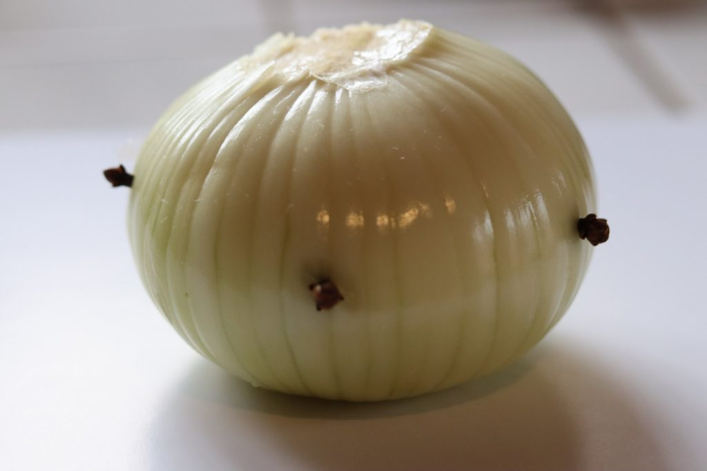 Onion pierces with 4 cloves for the French beef stew pot au feu