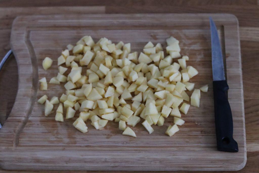 pommes pelées et coupées en morceaux sur une planche en bois et un couteau de cuisine