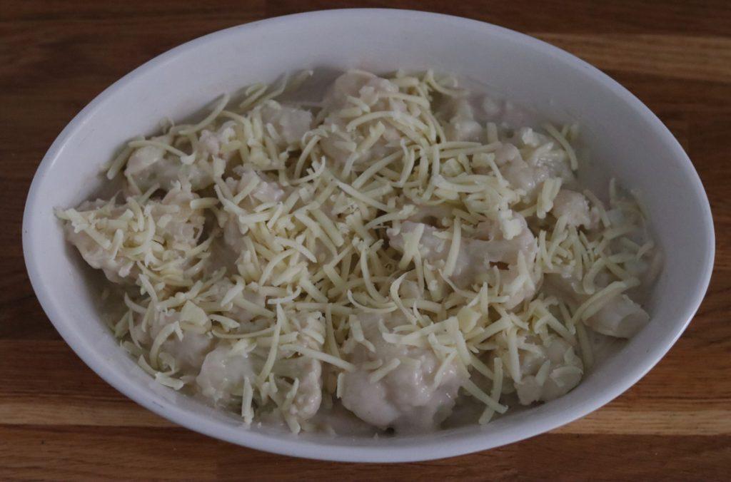 le chou-fleur recouvert de sauce béchamel et de fromage râpé dans un plat à gratin