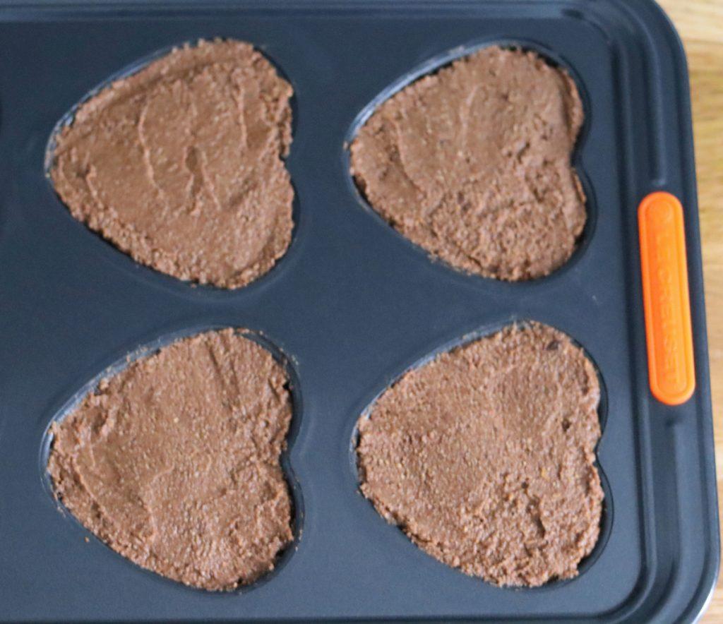la pâte à gâteau versée dans un moule à muffins en forme de coeur