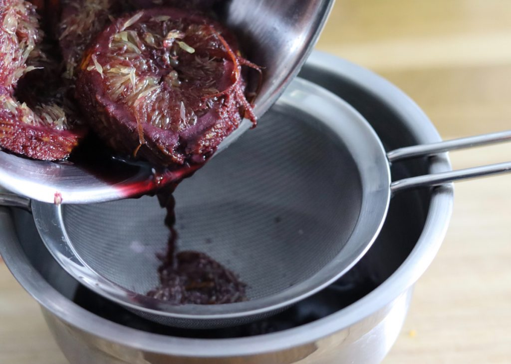 mulled wine being strained by transfering it in a large bowl with a strainer over the bowl