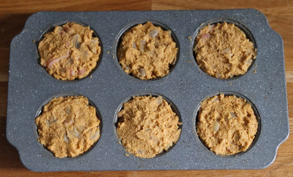 sweet potato and bacon muffin batter in a muffin pan