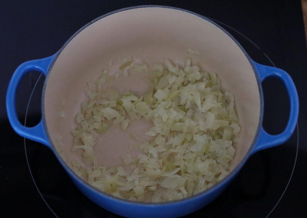 oignon émincé en train de suer dans une cocotte en fonte