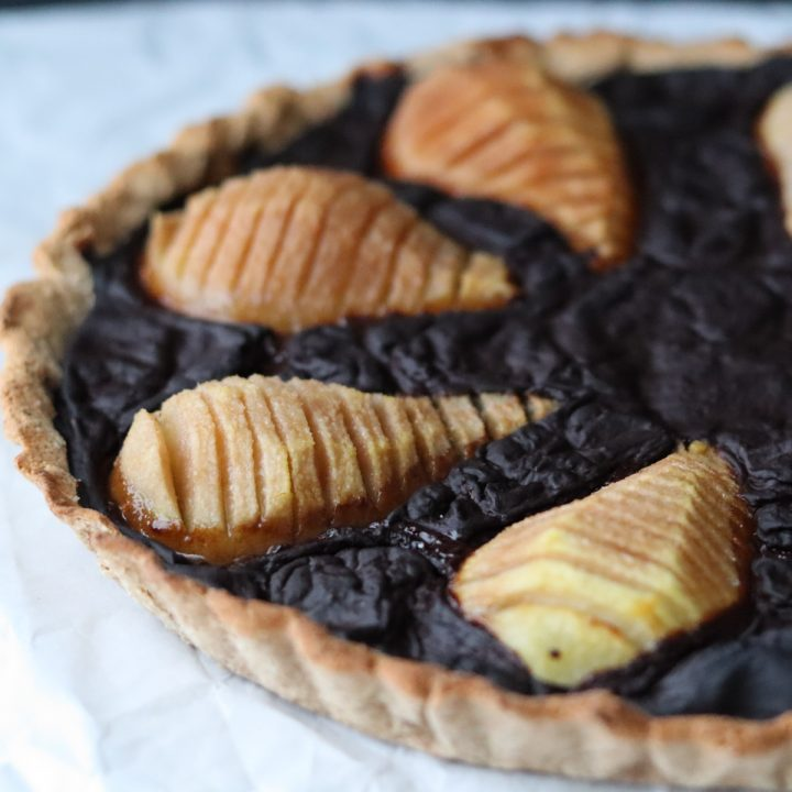 a pear and carob tart on a white sheet