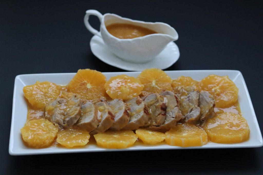 pork tenderloin and orange slices on a white plate and orange sauce in a sauce boat