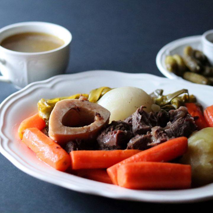 Beef stew in a large white plate and a cup of bone broth in the background with a plate of cornichons and coarse salt