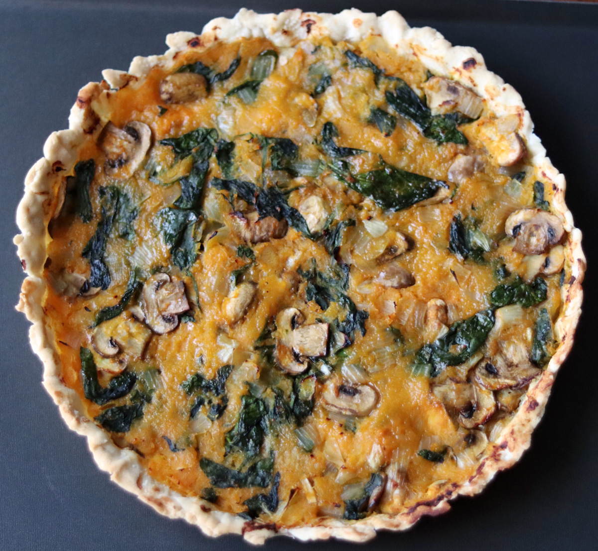 a pumpkin and spinach quiche on a black tray