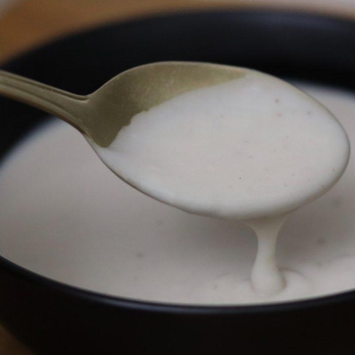 Vegan and gluten free Bechamel sauce in a black bowl