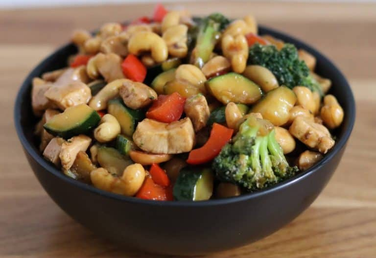 chicken stir fry in a black bowl