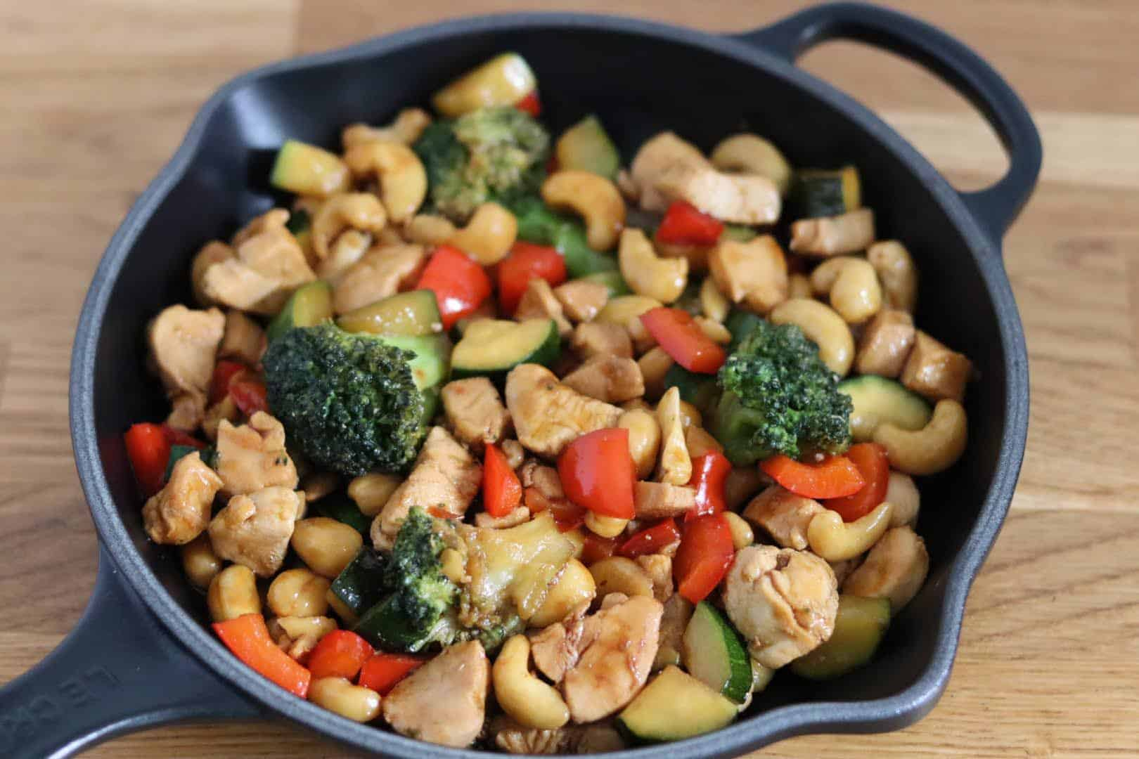 chicken stir fry in a black skillet