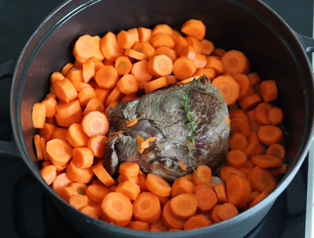 beef stew meat and sliced carrots cooking in a large black Dutch oven