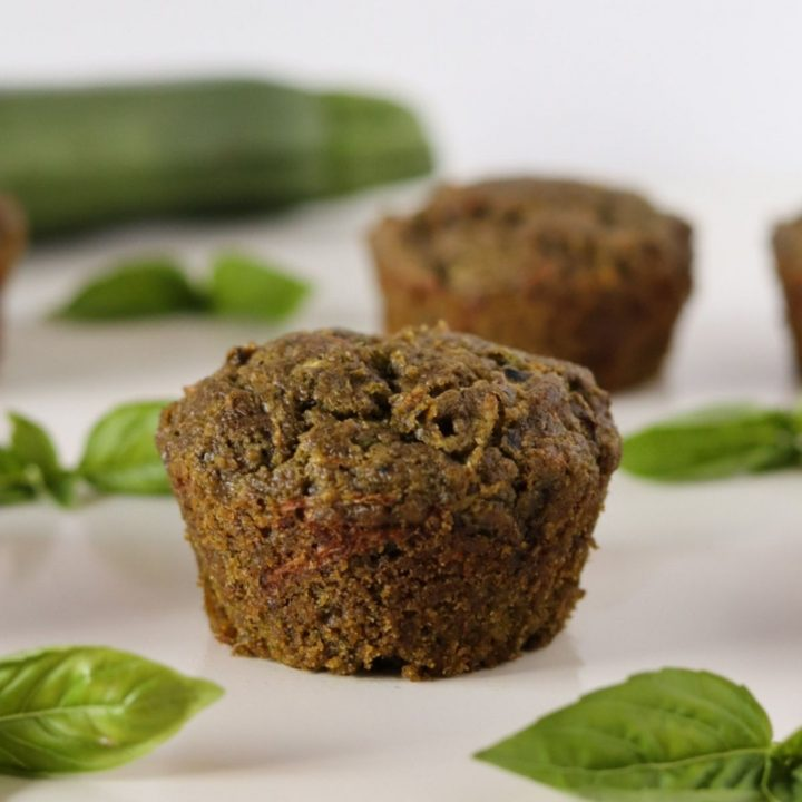 2 zucchini and pesto muffins basil leaves and a zucchini in the background