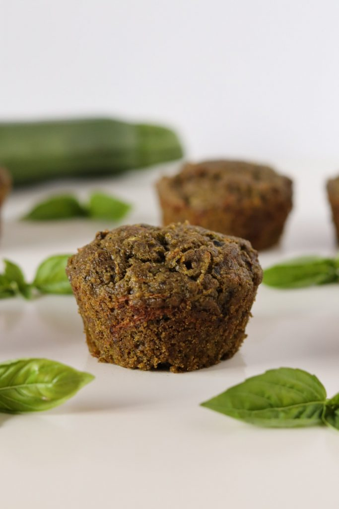3 zucchini and pesto muffins basil leaves and a zucchini in the background