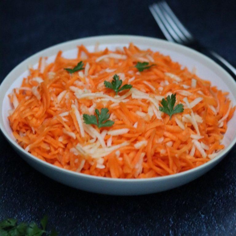 Salade de carottes râpées aux pommes dans une assiette creuse blanche et une fourchette en arrière plan