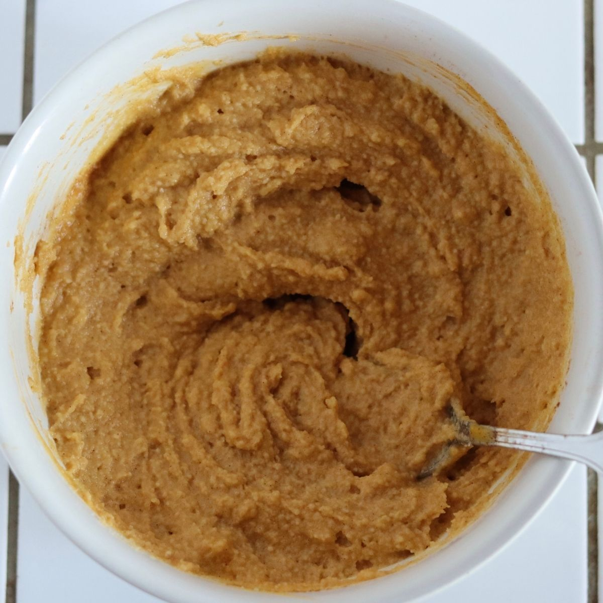 the paleo pumpkin muffins batter mixed with a spoon in a white bowl