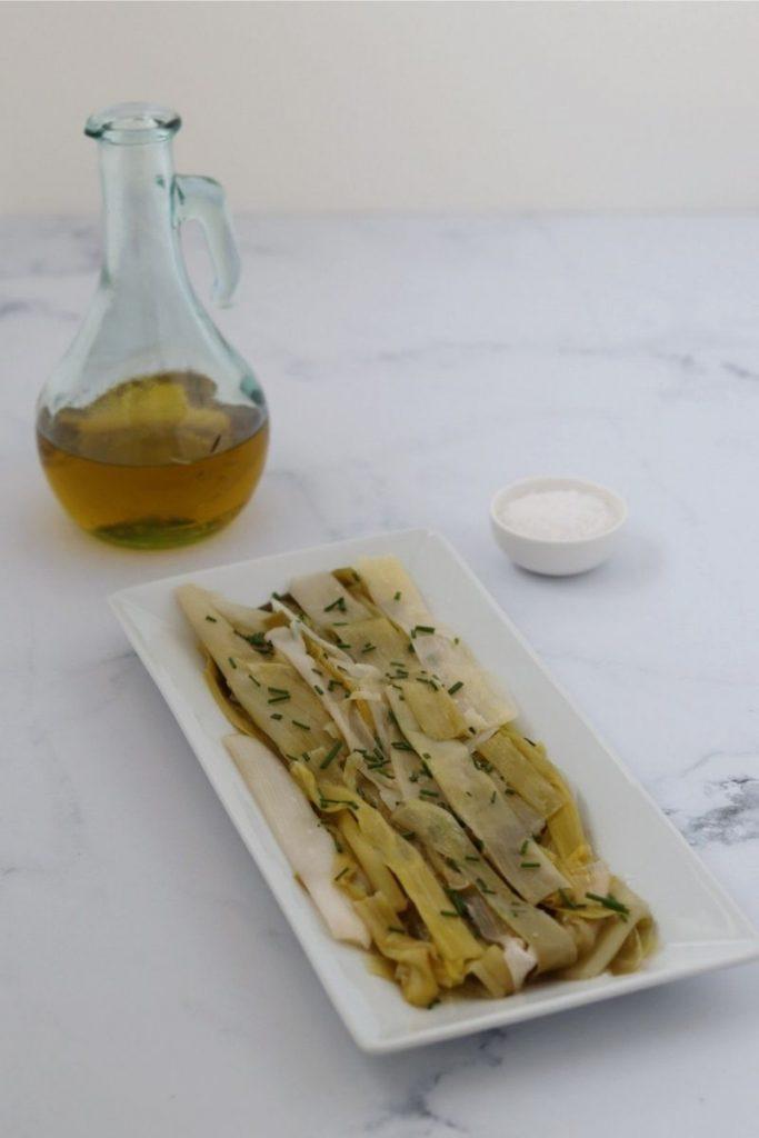 poireaux vinaigrette sur un plat rectangulaire blanc, un flacon d'huile d'olive et de la fleur de sel dans un petit bol