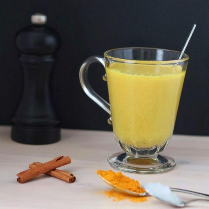 une tasse en verre pleine de lait d'or, un moule à poivre, 2 bâtons de cannelle, une cuillère pleine de curcuma et une cuillère plein d'huile de coco